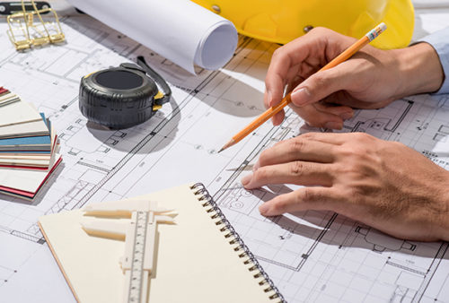 Working on blueprints. Construction project with tools and notebook.
