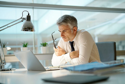 Businessman working on laptop in office, being concerned